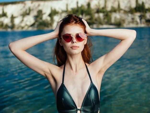 Sexy frau in einem grünen badeanzug und in den gläsern nahe einem durchsichtigen fluss in der natur