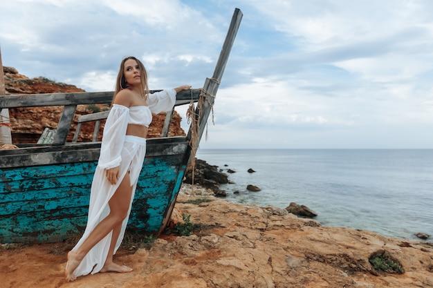 Sexy frau in einem weißen kleid auf einem schiffswrack an einer felsigen küste