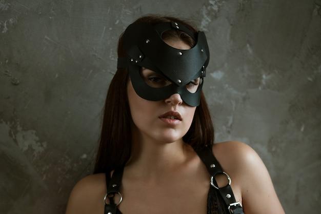 Sexy frau in einer maske und einem schwarzen body
