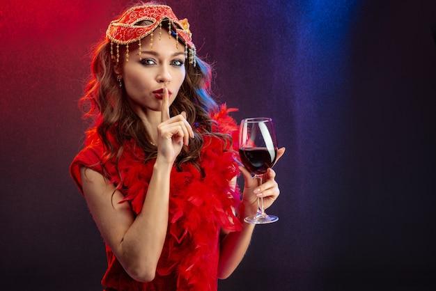 Sexy frau in einer roten karnevalskleidung mit einem angehobenen glas wein