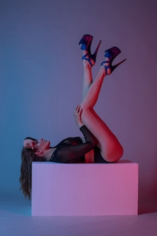 Sexy frau in high heels posiert auf einem würfel