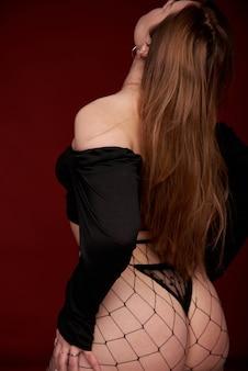 Sexy frau in schwarzen netzstrumpfhosen im studio auf rotem grund