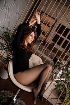Sexy frau in schwarzen strumpfhosen, die auf dem stuhl sitzen