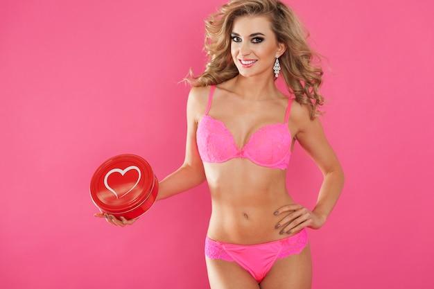 Sexy frau in unterwäsche und herzbox. happy valentinstag konzept