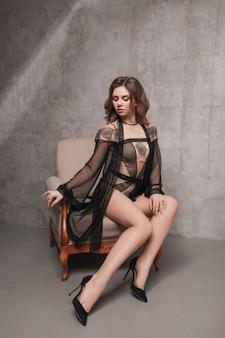Sexy frau in unterwäsche und peignoir sitzen auf einem stuhl