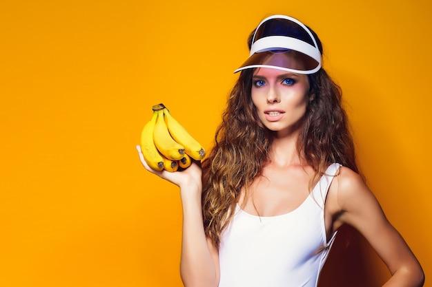Sexy frau in weißen badeanzug und blue jeans shorts, trendiges visier hält bananen und posiert isoliert über gelb