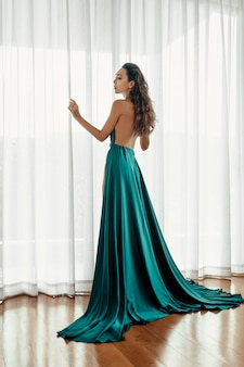 Sexy frau mit dem attraktiven make-upbraunhaar im herrlichen langen grünen kleid mit der bloßen rückseite, die nahe fenster mit weißen vorhängen aufwirft