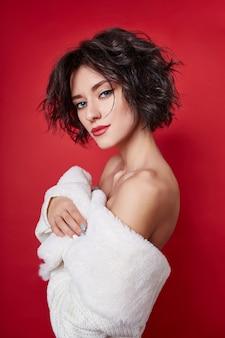 Sexy frau mit dem kurzen haar schnitt in weiße strickjacke