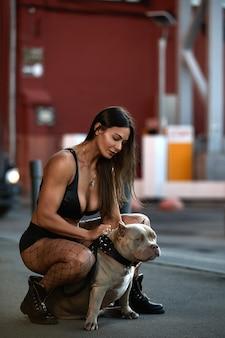 Sexy frau mit einer athletischen figur mit zwei hunden american bully auf den straßen der stadt