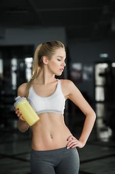 Sexy frau mit gelben flasche in der turnhalle