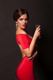 Sexy frau mit rotem kleid und alkohol