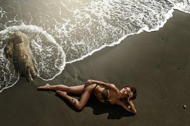 Sexy frau mit schönem körper liegt am strand