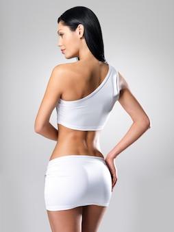 Sexy frau mit schönem schlanken körper - modell, das im studio aufwirft