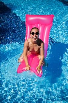 Sexy frau mit sonnenbrille, die sich auf einer rosa matratze im pool ausruht und ein sonnenbad nimmt. junge frau im beigen bikini-badeanzug, der auf aufblasbarer rosa matratze schwimmt
