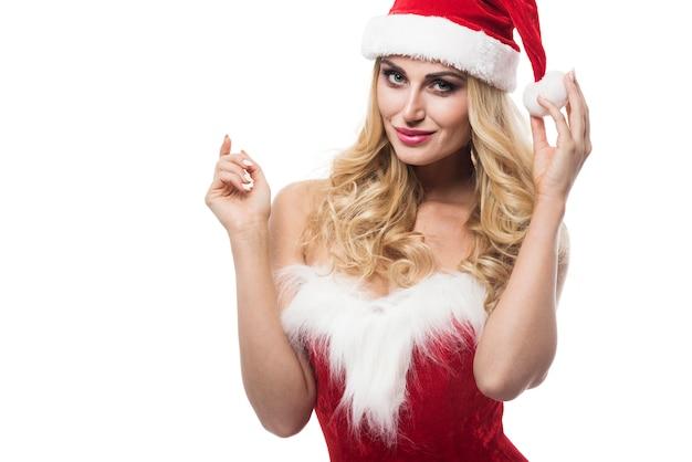 Sexy frau mit weihnachtsmütze, die auf weißer wand aufwirft