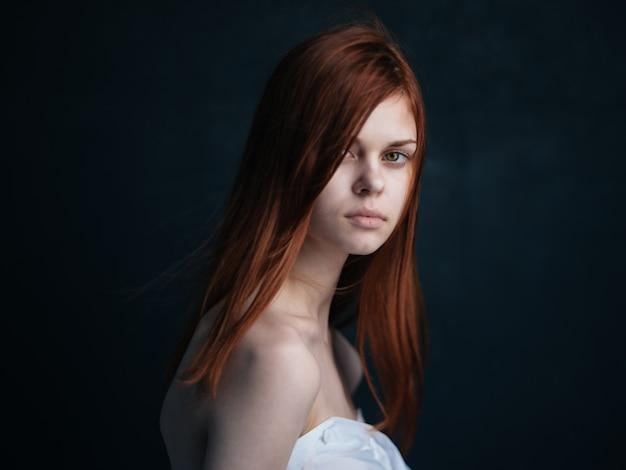 Sexy frau modell mit roten haaren auf einer schwarzen hintergrund nahaufnahme seitenansicht