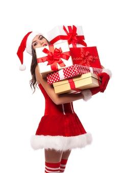 Sexy frau santa claus hält schweren stapel weihnachtsgeschenke