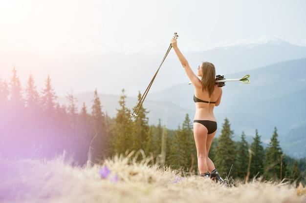 Sexy frau skifahrer genießt warmen frühling, trägt badeanzug, stiefel und sonnenbrillen