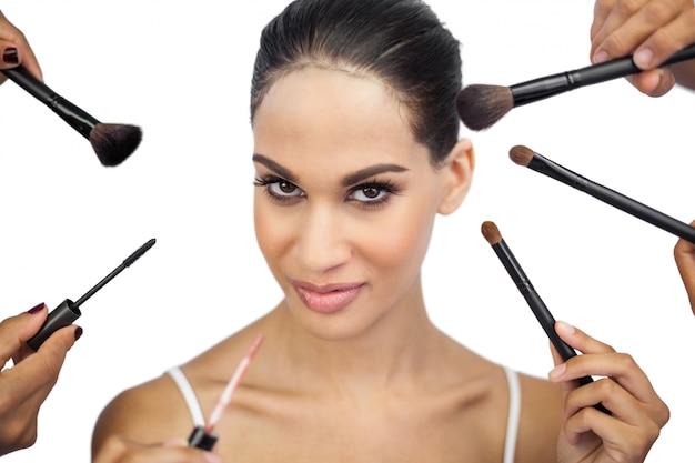 Sexy frau, umgeben von make-up-bürsten