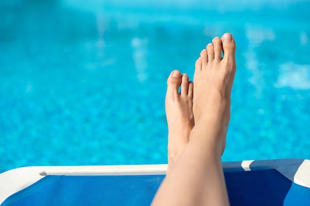 Sexy frauen beine pediküre nägel spritzen im tropischen schwimmsommerpool