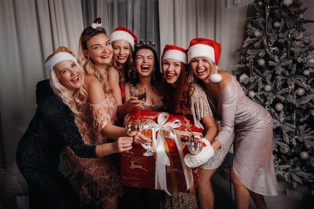Sexy frauen in weihnachtsmützen mit gläsern champagner und einem großen geschenk.