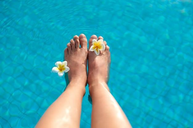 Sexy frauenbein-pedikürenägel, die im tropischen schwimmensommerpool spritzen