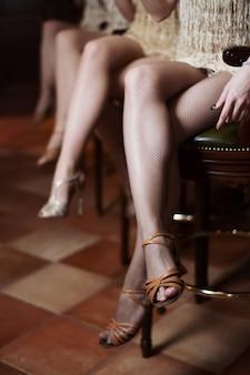 Sexy frauenfüße in vergoldeten schuhen und kleidern