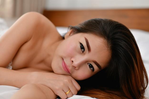 Sexy frauenkonzept. sexy asiatische mädchen spielen im schlafzimmer.