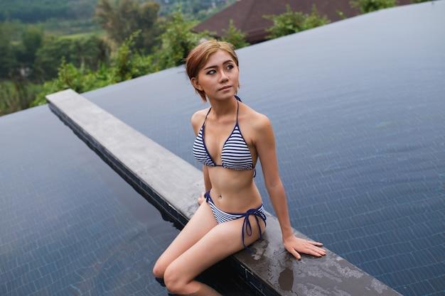 Sexy frauenporträt im bikini am swimmingpool