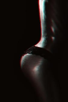 Sexy gesäß eines mädchens im höschen mit wassertropfen auf ihrem körper nahaufnahme. silhouette eines sportlich schlanken weiblichen körpers