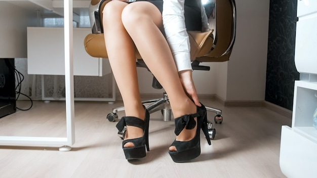 Sexy geschäftsfrau im rock, die schuhe mit hohen absätzen im büro auszieht.