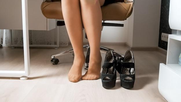 Sexy geschäftsfrau in strümpfen, die im bürosessel sitzt und schuhe mit hohen absätzen auszieht.