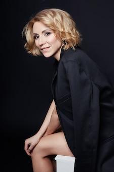 Sexy geschäftsfraublondine des porträts im schwarzen kleid