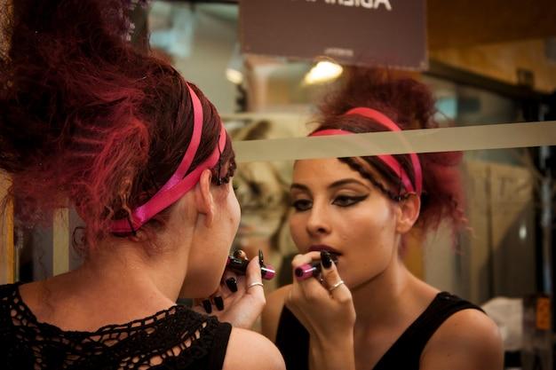 Sexy girl schminkt sich selbst im spiegel