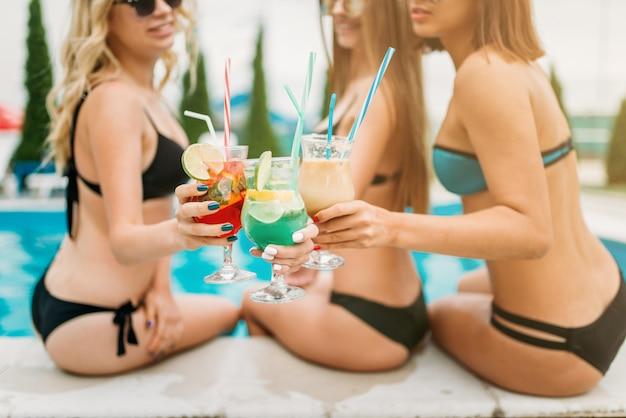 Sexy girls haben spaß am pool, resorturlaub. gebräunte frauen entspannen sich im schwimmbad