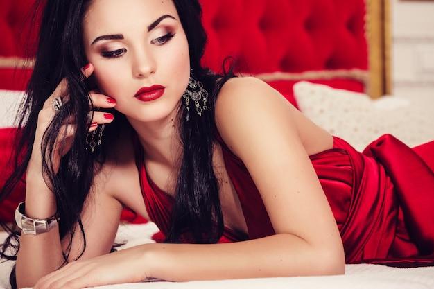 Sexy glamourfrau mit schwarzen haaren im eleganten roten kleid im luxusschlafzimmer