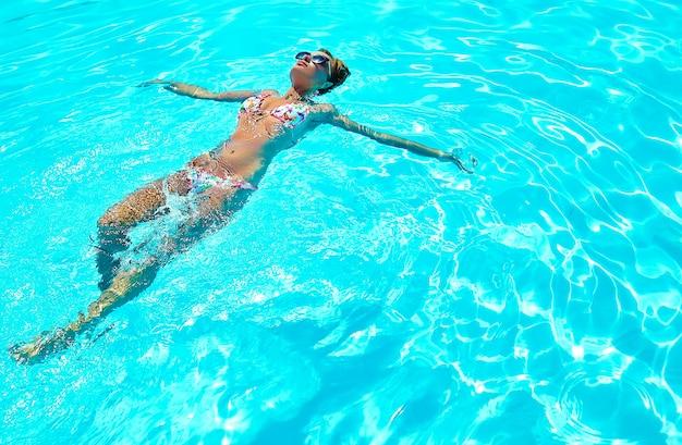 Sexy heißes schönes mädchenmodell mit dunklem haar in der bunten badebekleidung, die auf rücken schwimmt