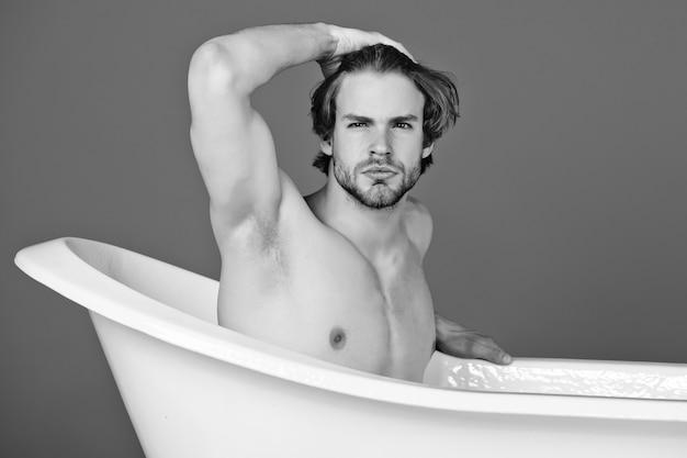Sexy homosexuell in der badewanne. kerl in der badewanne. spa und schönheit, entspannung und hygiene, gesundheitswesen.