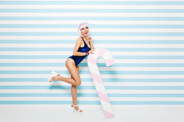Sexy hübsches modisches modell im blauen body, der sommer auf blau-weiß gestreifter wand genießt. tragen geschnittene rosa frisur, absätze, strandmütze. attraktive junge frau, aufgeregt, ausdruck der positivität.