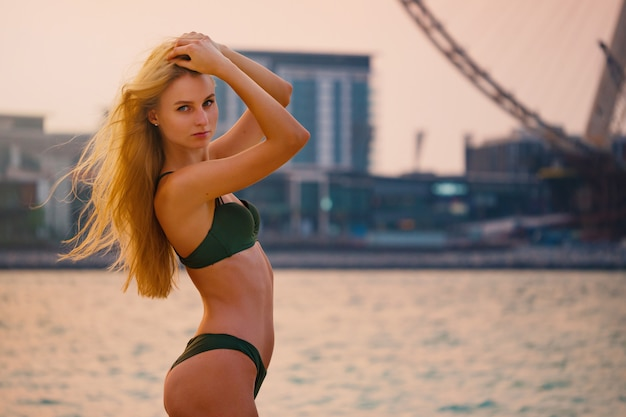 Sexy junge blonde frau, die bikini am strand trägt