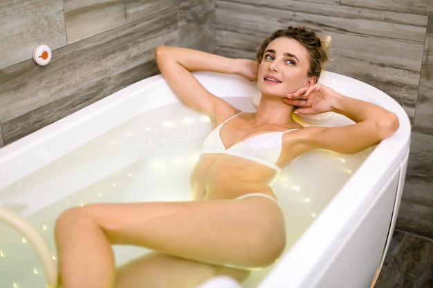 Sexy junge blonde frau im weißen badeanzug posiert und entspannt in der badewanne, die eine hydromassagetherapie im spa hat