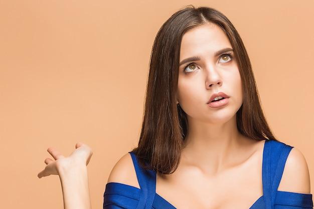 Sexy junge brünette frau, die mit dem finger in einem blauen kleid im studio auf braunem hintergrund zeigt