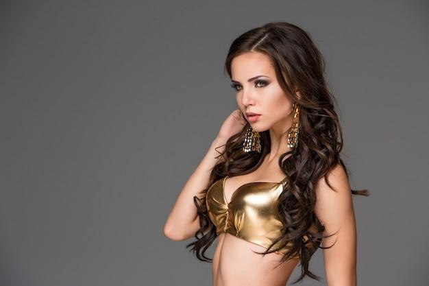 Sexy junge brunettefrau mit ihrem haar, das in einem goldbikini aufwirft.