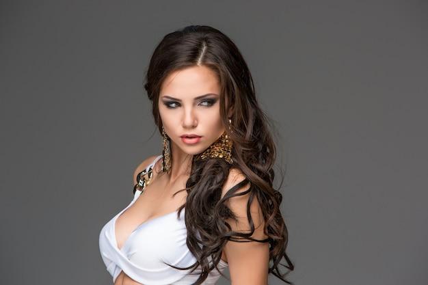 Sexy junge brunettefrau mit ihrem haar, das in einem weißen bikini aufwirft. studio