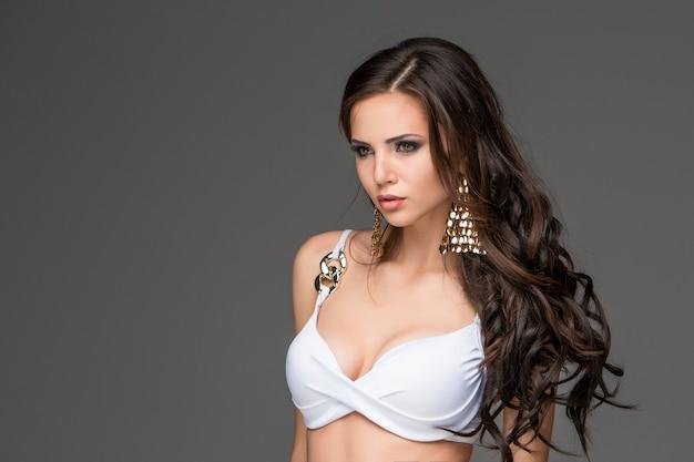 Sexy junge brunettefrau mit ihrem haar, das in einem weißen bikini aufwirft.