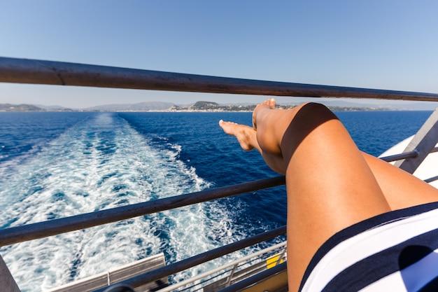 Sexy junge frau beine, die auf kreuzfahrtschiffreiseurlaub entspannen