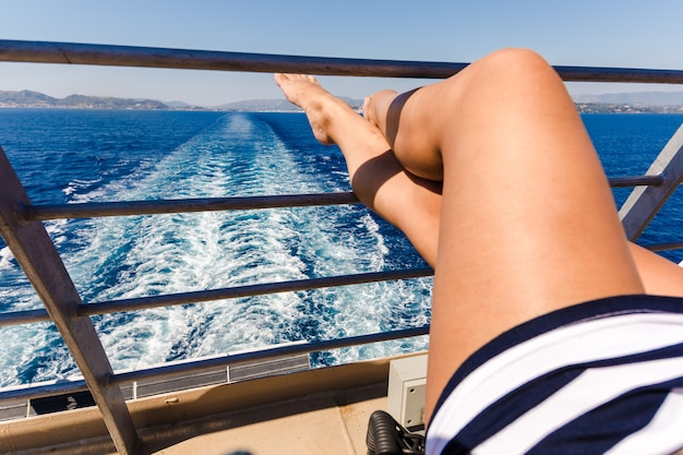 Sexy junge frau beine, die auf kreuzfahrtschiffreiseurlaub entspannen.