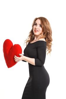 Sexy junge frau des valentinstags mit den roten lippen, die das selbst gestaltete herz im schwarzen kleid halten. modefrau, die schwarzes kleid mit großem rotem herzen trägt. valentinstag.
