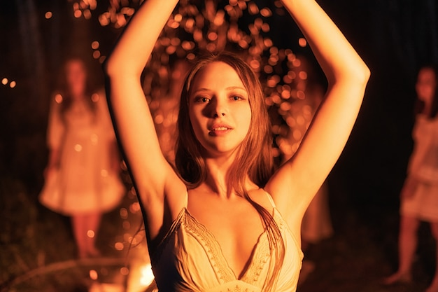 Sexy junge frau, die am lagerfeuer tanzt.
