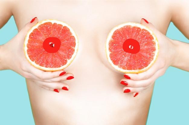 Sexy junge frau, die grapefruits nahe ihren brüsten auf farbhintergrund hält.
